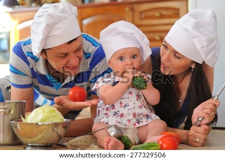 Young family with looking hoods on their heads: a little cute baby-girl is sitting on the kitchen floor, she is eating cucumber - her parents are lying next to her smiling and playing cooks - stock photo
