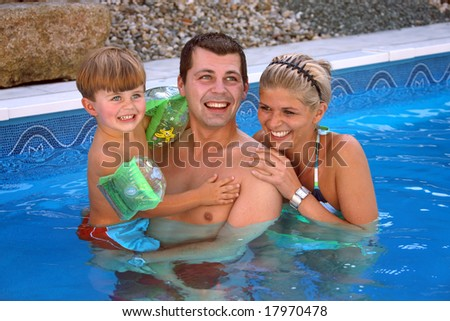 Young family with one child in the pool - stock photo