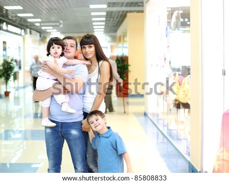 Young family with shopping bags doing shopping - stock photo