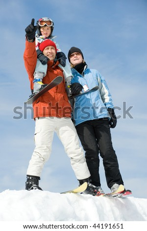 Young family with ski in front of blue sky - stock photo