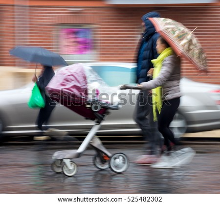 Young family with small child in the stroller walking down the street in a rainy day.  Woman with umbrella. Intentional motion blur