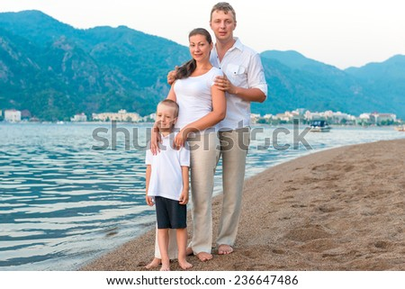 young family with son on the beach on vacation - stock photo