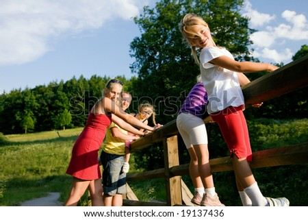 Young family with three children standing on a bridge in the sunlight, focus on girl in front - stock photo