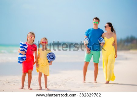 Young family with towels on vacation - stock photo