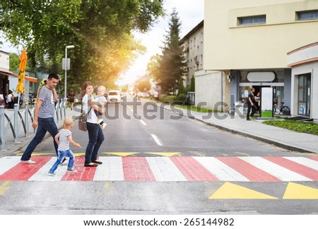 Young family with two boys in the city walking on a crosswalk