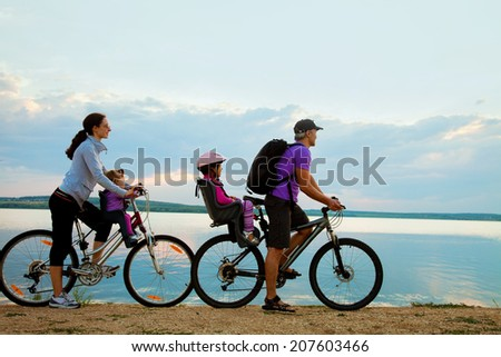 Young family with two kids go for a cycle ride on the beach at background sunset - stock photo