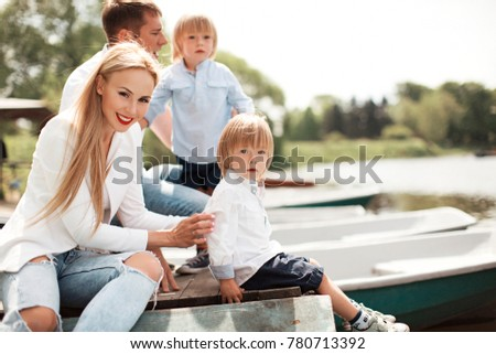 Young family with two kids twins boys outdoors in park