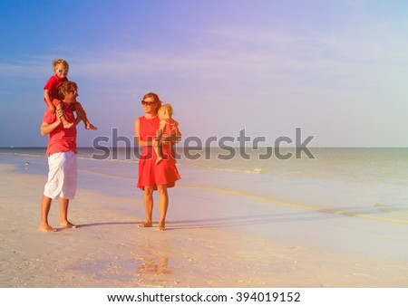 Young family with two kids walking at beach