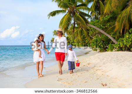 Young family with two kids walking at tropical beach, family beach vacation - stock photo