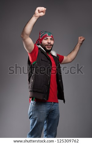 young fan standing with his hands in the air and cheering - stock photo