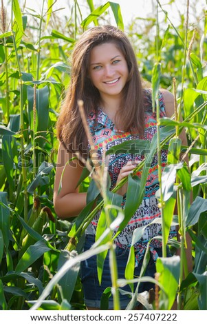 Young farm girl portrait at green corn field background - stock photo