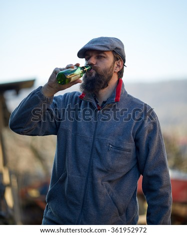 Young farmer drinking a bottle of beer in the courtyard - stock photo