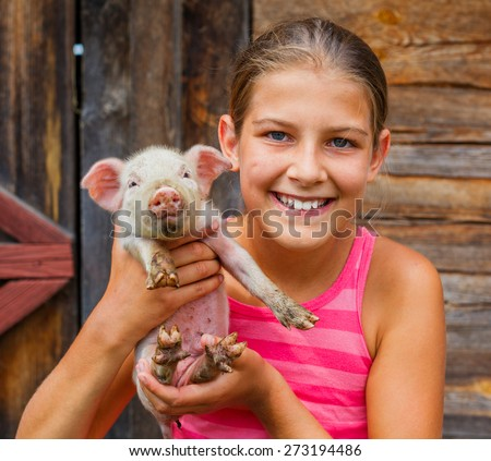 Young farmer - Happy girl holding a white piglet in her hands.