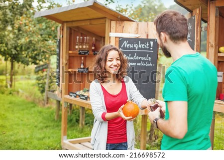 Young farmer selling vegetables - stock photo