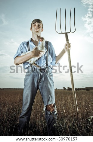 Young farmer standing in his farm holding a fork - stock photo