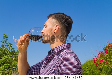 Young farmer tastes a glass of red wine in the vineyard. - stock photo