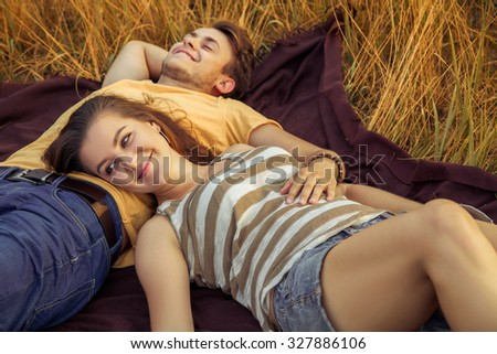 young fashion beautiful loving casual style couple  lying down on floral field in autumnal park, warm sunny day, enjoying family, romantic date, happiness and love concept. smile and happiness. - stock photo