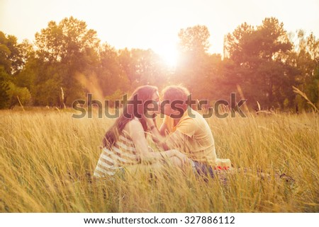 young fashion beautiful loving casual style couple lying down on floral field in autumnal park, warm sunny day, enjoying family, romantic date, happiness and love concept. hug and kiss. - stock photo
