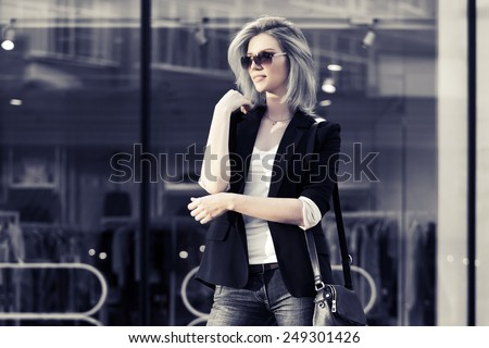 Young fashion blond business woman against a mall window - stock photo