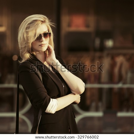 Young fashion blond business woman in sunglasses at the mall window - stock photo