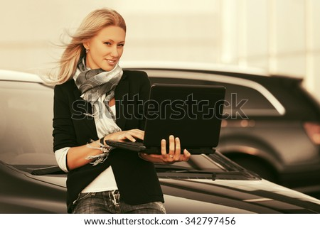 Young fashion blond business woman with laptop next to her car - stock photo