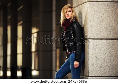 Young fashion blond woman in leather jacket at the wall - stock photo
