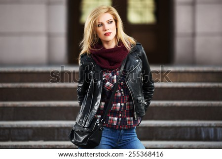 Young fashion blond woman in leather jacket on the steps - stock photo