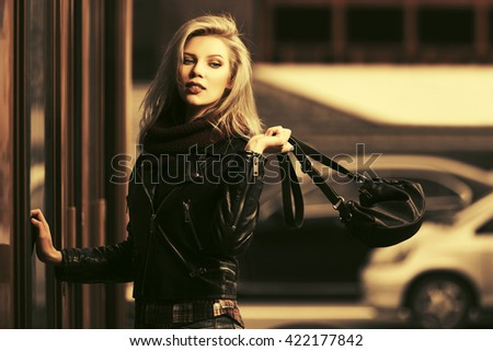 Young fashion blond woman in leather jacket with handbag - stock photo