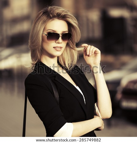 Young fashion blonde business woman in sunglasses on a city street - stock photo