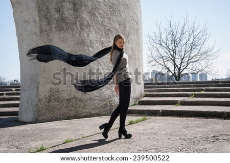 Young fashion blonde girl wearing long black scarf on the background of the futuristic building - stock photo