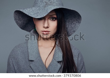 young fashion brunette woman beauty portrait posing in studio wearing in gray coat and hat - stock photo