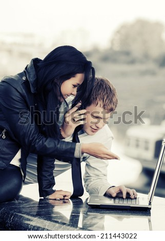 Young fashion business couple using laptop outdoor - stock photo