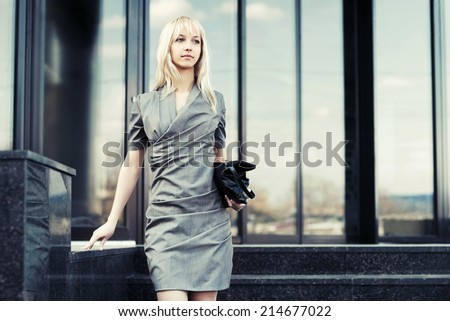 Young fashion business woman against office windows  - stock photo