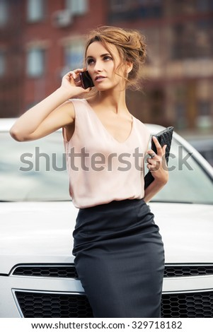 Young fashion business woman calling on mobile phone beside a car - stock photo