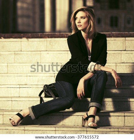 Young fashion business woman sitting on the steps - stock photo