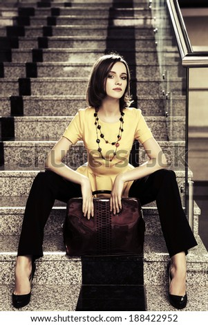 Young fashion business woman sitting on the steps in office interior - stock photo