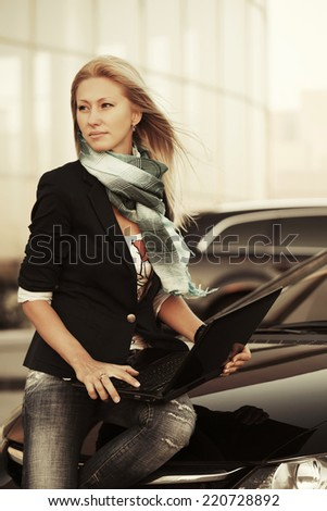 Young fashion business woman with laptop at the car  - stock photo