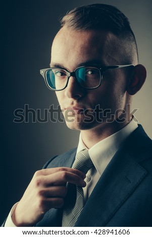 young fashion businessman with nerd glasses and stylish hairdo in jacket straightening tie posing on grey background