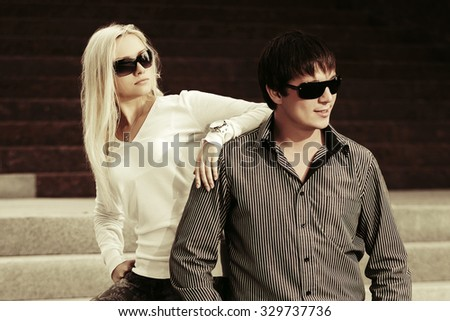 Young fashion couple in sunglasses on the steps - stock photo