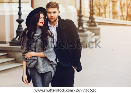Young fashion couple posing on the old  street in  sunny fall . Pretty beautiful  woman and her  handsome stylish boyfriend  hugging  on the street. Creamy  autumn sunlight. - stock photo