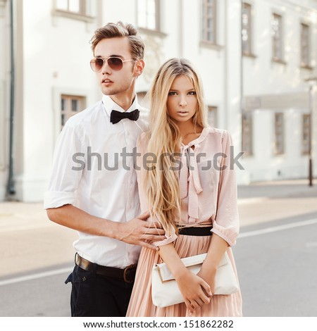 Young fashion couple posing outdoor in summer. Handsome man and pretty beautiful woman outdoor vintage portrait. - stock photo