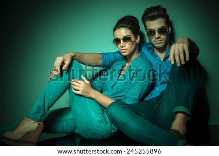 Young fashion couple sitting and leaning on a wall while looking at the camera. - stock photo