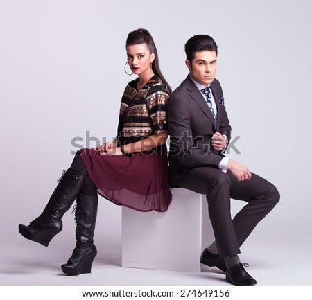 Young fashion couple sitting on a white table back to back. - stock photo