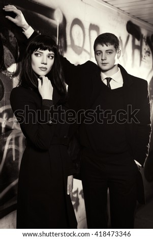 Young fashion couple standing at the graffiti wall. Male and female fashion model - stock photo