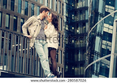 Young fashion couple walking down the street in summer near skyscraper. Pretty beautiful woman in stripes  clothes. Creamy sunlight - stock photo