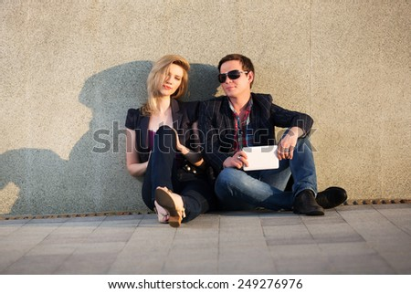 Young fashion couple with tablet computer sitting at the wall - stock photo