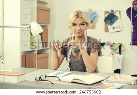 Young fashion designer working at studio - stock photo