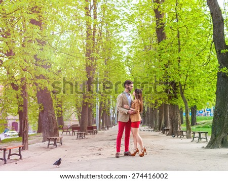Young fashion elegant stylish couple, in love , stand opposite each other on park in spring sunny weather - stock photo