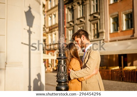 Young fashion elegant stylish couple posing on streets of european city in summer, near lamppost on the wall display them shadow silhouette - stock photo