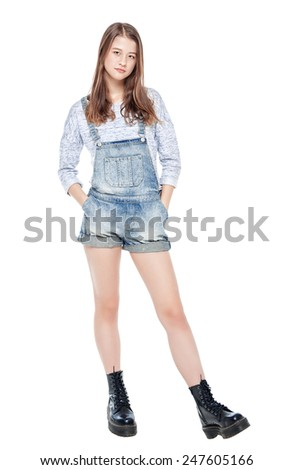 Young fashion girl in jeans overalls posing isolated on white background - stock photo